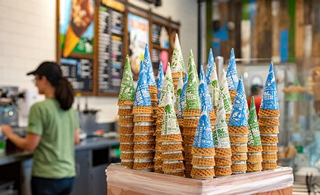 A Ben & Jerry's ice cream cone being handed to a customer